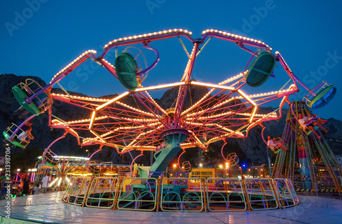 Fotografiet Colorful carousel spinning in the amusement park at night.