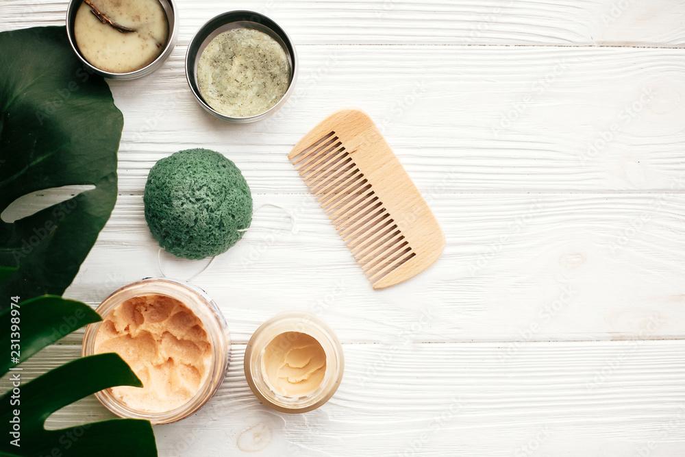 Fototapeta Natural eco friendly solid shampoo bar, wooden brush,  deodorant cream, scrub and konjaku sponge on white wood with green monstera leaves. Zero waste products plastic free