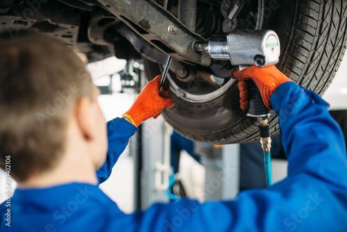 Fotografie, Obraz Technician with a wrench repair car suspension