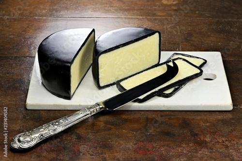 angeschnittener Cheddarkäse mit Silbermesser und Keramikbrettchen auf rustikalem Holztisch