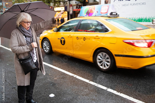 Photographie Mature senior white haired woman waiting for taxi cab in New York