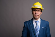 Young Asian Businessman Wearing Hardhat Against Gray Background