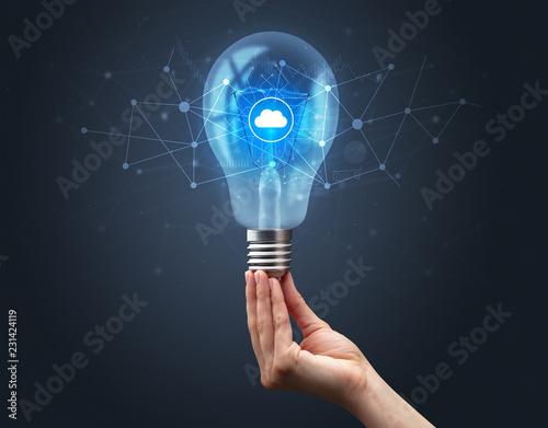 Fotomural  Hand holding light bulb on dark background