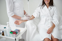 Anti-stress Procedure. Cropped Portrait Of Female Doctor In Sterile Gloves Preparing Lady Hand For IV Infusion. Brunette Girl In White Bathrobe Smiling
