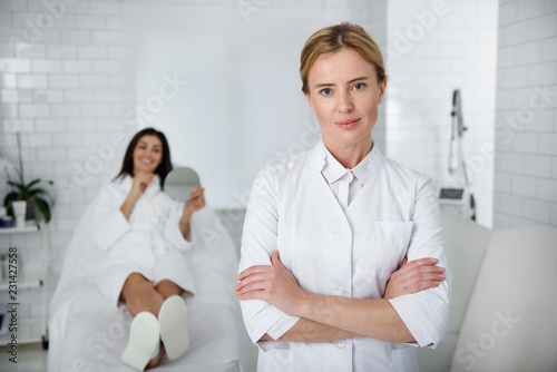 Photo  Waist up portrait of beautiful lady in white lab coat crossing arms and looking at camera with smile