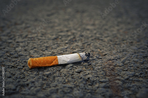 closeup of smoking cigarette butt on asphalt with copy space Slika na platnu