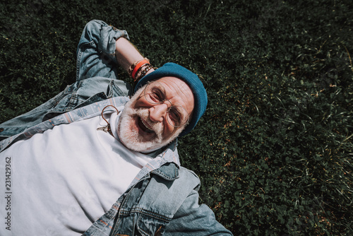 Fotografija Top view of happy pensioner man lying on grass and holding hand behind head