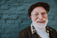 Close Up Portrait Of Happy Emotional Pensioner Smiling And Standing Near Gray Wall Outdoor. Copy Space On Left Side