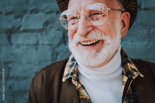 Close up portrait of cheerful pensioner staying near gray brick wall and smiling