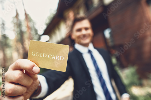 Fotografía  Young man standing outdoors and showing his useful gold card