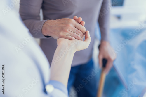 Fototapety, obrazy: Focus on top view close-up of medical worker supporting woman. Patient is using crutch and leaning on physician arm while they are connecting palms