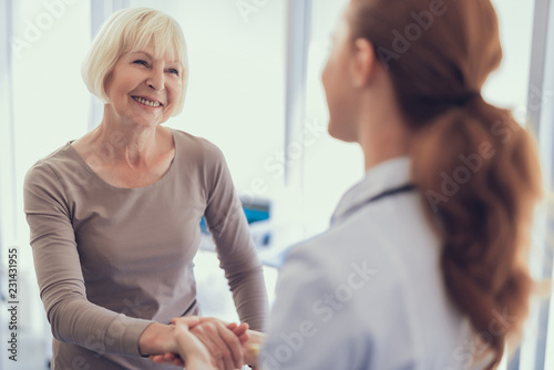 Focus on smiling lady shaking hands with physician after visit to clinic. She is feeling very grateful for receiving medical treatment. Copy space in right side