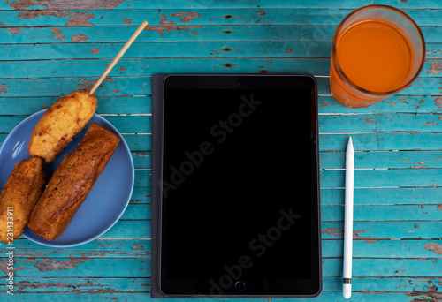 Black screen pad, orange juice and snacks on green table Canvas Print