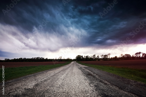Fotografie, Obraz  Storm clouds over a country road
