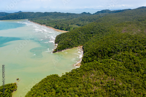 Fotomural Aerial drone view of dense tropical rainforest leading to a remote, rough ocean