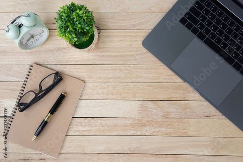 Fototapeta Business office desk with laptop, alarm clock and supplies. on wooden background. Top view with copy space, flat lay. obraz na płótnie