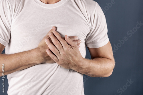 Fotografía  Man holding his chest with both hands, having heart attack or painful cramps, pressing on chest with painful expression on blue backgound