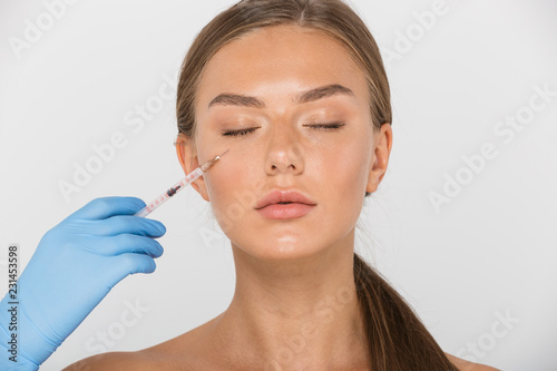 Beauty portrait of young shirtless woman in glove making injection with syringe, isolated over white background