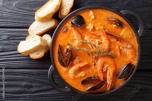 Seafood spicy soup with potatoes, shrimps, mussels, herbs and fish from a picad closeup served with toast. Horizontal top view