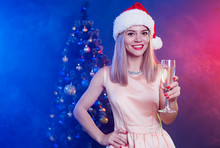 Happy Beautiful Young Smiling Blonde Woman In Santa Hat With Champagne In Hand Is Posing On Christmas Tree Colorful Purple Background On The Party