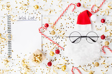 Christmas Background Of Golden Confetti, Gift Or Present Boxes, Wish List Notebook And Funny Santa On White Table Top View. Flat Lay.