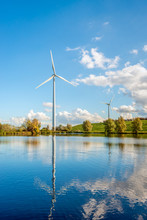 Electricity Generating Wind Turbines Reflected In The Water Surface Of A Small Lake