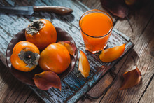 Ripe Orange Persimmon Fruit And Persimmon Leaves In A Brown Plate On A Brown Wooden Table
