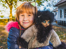Cute Little Girl Playing With Her Favorite Doll-puss Outdoor.Autumn Break At School.