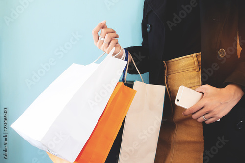 Valokuva  Woman in black overcoat with shopping bag and smartphone in hands