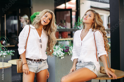 Photo  Positivity and pretty girls wearing similar in jeans shorts and white shirts, posing outdoor near cafe, showing peace