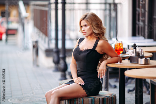 2d2b16af298 Sexy girl sitting on chair in cafe and drinking tasty cocktail ...