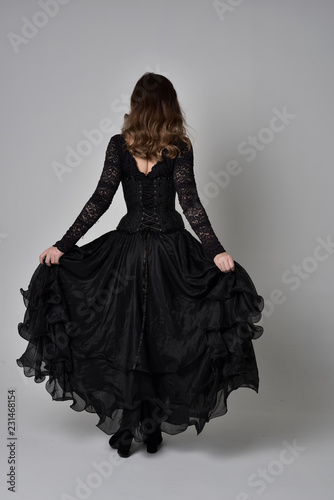 Foto  full length portrait of brunette girl wearing long black lace gown with corset
