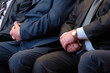 Male hands closeup. Abstract middle-aged men in a suit of an official or a businessman at a meeting. Wristwatches, shirt, tie.