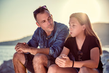 Father And Daughter Sitting On A Rocky Beach And Talking