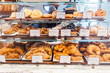 Various freshly and warm baked bread rolls on the shelf and ready to sell. Homemade by artisan.