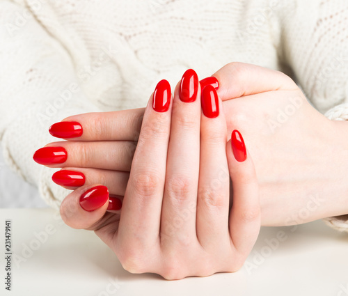 Fotomural young woman with red manicure on nails