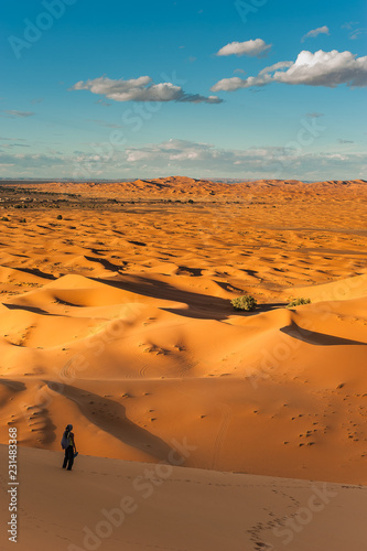 Staande foto Oranje eclat Girl stands on the dune erg chebbi and observes the desert landscape in merzouga morocco