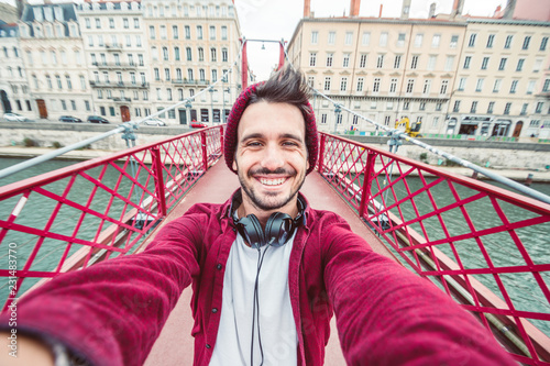 Fotografia  Casual man smile at the camera taking a selfie in the city on travel