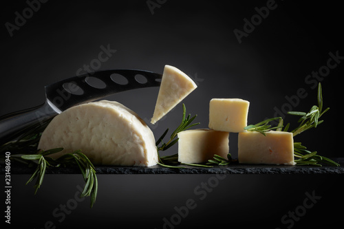 Sheep cheese with rosemary on a black background.