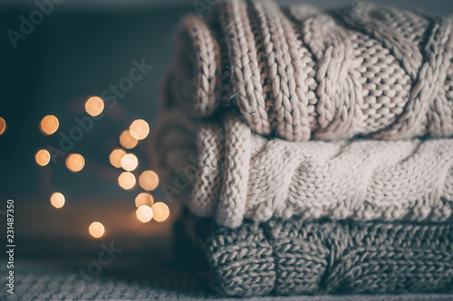 Stack of cozy knitted sweaters and garland lights on wooden background. Autumn-winter concept. Magic, cozy and mood time