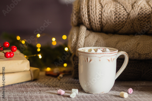 Stack of cozy knitted sweaters and cup of coffee or hot chocolate with marshmallow on wooden background. Autumn-winter concept. Magic, cozy and mood time