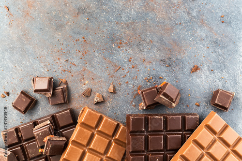 Milk and dark chocolate bars on a grey table. Top view