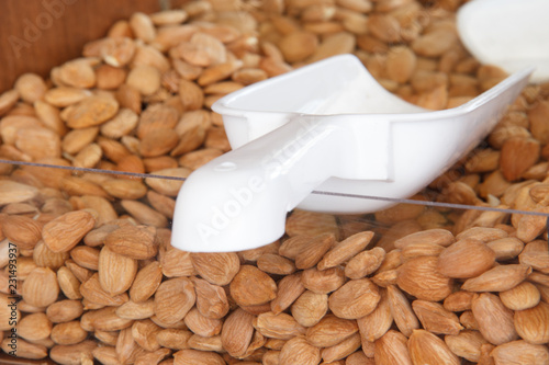 Fotografía  almond nuts on the counter of the store with scoop for typing