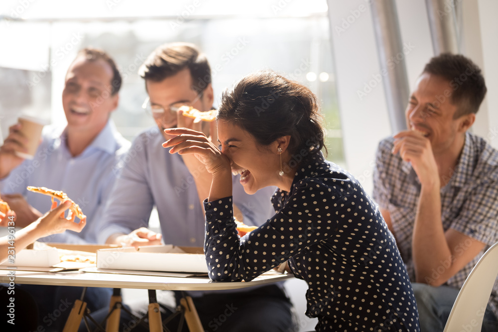 Fototapeta Indian woman laughing at funny joke eating pizza with diverse coworkers in office, friendly work team enjoying positive emotions and lunch together, happy colleagues staff group having fun at break