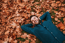 Young Man Lying Down On The Ground Covered In Autumn Leaves