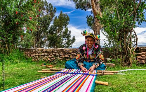Młoda kobieta z Peru tkająca wełnę alpaki na gobelin