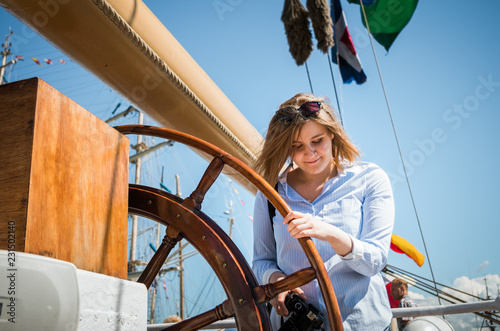Foto auf AluDibond Schiff Ginger girl smiling behind the steering wheel of an old sailing ship.