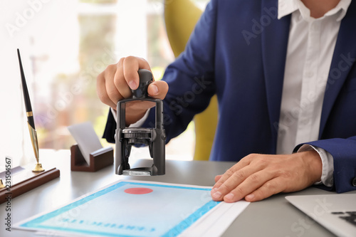 Notary stamping document at desk in office, closeup Canvas Print