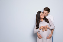 Pregnant Woman And Her Husband Holding Little Shoes On Color Background. Space For Text