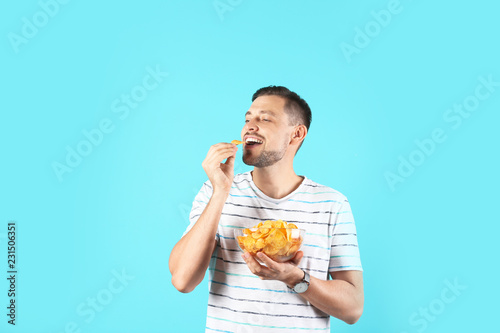 Man eating potato chips on color background